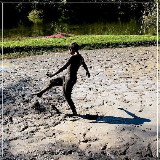 menino na piscina de lama